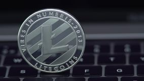 4K Physical metal silver Litecoin currency on notebook computer keyboard LTC. 4K Physical metal silver Litecoin currency on notebook computer keyboard. New stock footage