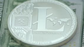 4K Physical metal silver Litecoin currency over 100 american dollar bill. 4K Physical metal silver Litecoin currency over 100 dollar bill of United States stock video