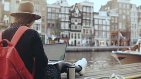 4K piękna Młody blogger pracuje z laptopem amsterdam Wolność Dziewczyna z czerwonym plecakiem w eleganckim kapeluszu na rzecznym  zbiory wideo