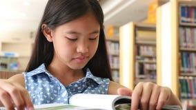 4K: Piccoli studenti asiatici che leggono un libro stock footage