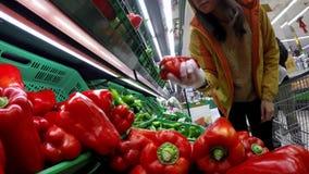 4K, pimientas rojas que hacen compras de la mujer asiática en el supermercado español Comida vegetal metrajes