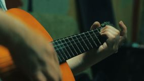 4k of playing acoustic guitar. Handsome men tune acoustic guitar.  stock footage