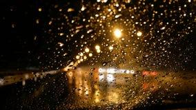 4K pleuvoir le fonctionnement vers le bas sur la fenêtre de voiture avant la nuit avec le bokeh du réverbère et du feu de signali banque de vidéos