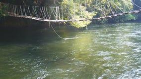 4K a ponte de suspensão feita com placas velhas das madeiras para passar sobre um rio pequeno com manhã expõe ao sol o brilho da  filme