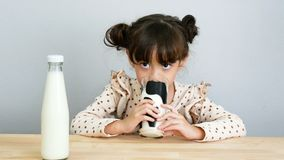 4K. portrait of adorable girl drinking fresh milk with funny face stock video footage