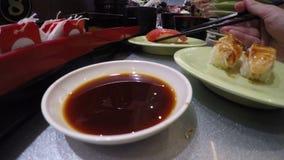 4K, povos preparam e comem o sushi no restaurante de Japão, conhecido como o trem do sushi video estoque