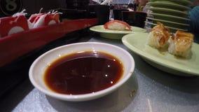 4K, povos preparam e comem o sushi no restaurante de Japão, conhecido como o trem do sushi vídeos de arquivo