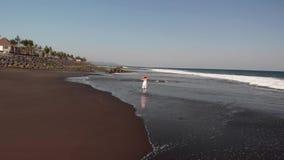 4K Powietrzny latający materiał filmowy młoda kobieta w biel sukni odprowadzeniu na czarnej powulkanicznej plaży, Bali wyspa zbiory wideo