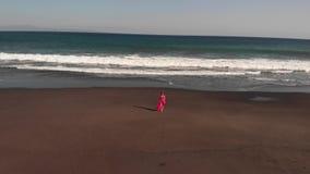 4K Powietrzny latający materiał filmowy młoda kobieta w menchiach ubiera odprowadzenie na czarnej powulkanicznej plaży, Bali wysp zbiory wideo