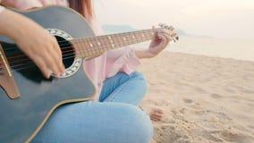 4K próximo acima da mulher longa do cabelo jogar a guitarra acústica na praia com vento delicado durante o tempo do por do sol, s video estoque