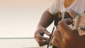 4K próximo acima de um homem jogar a guitarra acústica na praia durante o tempo do por do sol, sentimento relaxa video estoque