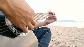 4K próximo acima de um homem jogar a guitarra acústica na praia durante o tempo do por do sol, sentimento relaxa filme