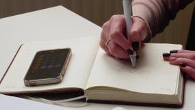 4K Primer de las manos femeninas que escriben notas en organizador personal y que usan la calculadora en smartphone El usar de la almacen de metraje de vídeo