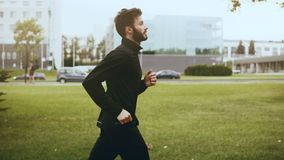 4K profil sportowa bieg post blisko miasto ulicy Czas rzeczywisty Boczny widok Przystojnego brodatego Europejskiego mężczyzna jog zdjęcie wideo