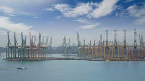 4K Puerto de envío de Singapur con el buque de carga que navega lentamente en el mar y mucho envase y grúas amarillas en fondo almacen de video