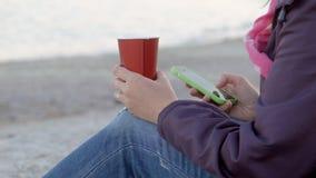 4K que a mulher se senta na praia com o copo da bebida quente e se usa seu telefone Perto disparado acima atrás da parte traseira video estoque