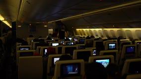 4K que viaja por el aire Cabina del aeroplano con los pasajeros que miran películas de los monitores almacen de metraje de vídeo