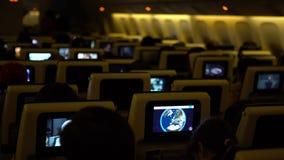4K que viaja por el aire Cabina del aeroplano con los pasajeros que miran películas de los monitores metrajes
