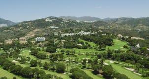 4K que vuela sobre un vídeo de la antena del campo de golf Campo de golf de Marbella cerca de las montañas España 2016 HD almacen de video