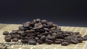 4k a rôti des grains de café tourne sur le fond noir Ingrédient pour le café banque de vidéos