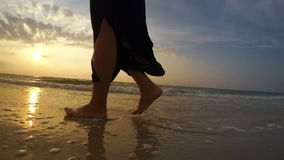 4K real-time footage of a woman walking along the beach at sunset stock video