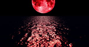 A 4K red colored moon setting slowly over the ocean at night with the color of the moon reflecting light onto the ocean waves stock video
