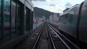 4K regardant hors de la fenêtre des voies mobiles d'un train de voiture de métro dans la ville de Busan banque de vidéos