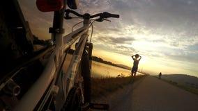 4k resolutie: weinig fietser die van de zonsondergang genieten tijdens rust pauze stock footage