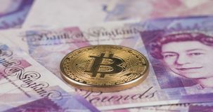 4k resolution of a cryptocurrency gold Bitcoin coin on a British Pound Sterling bills. Close-up, macro shot - pan
