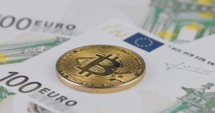 4k resolution of a cryptocurrency gold Bitcoin coin on a hundred euro bills. Close-up, macro shot - pan movement