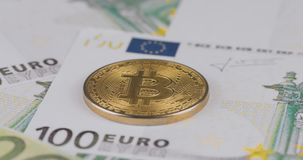 4k resolution of a cryptocurrency gold Bitcoin coin on a hundred euro bills. Close-up, macro shot - rotating in circle