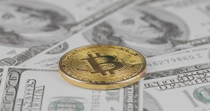 4k resolution of a cryptocurrency gold Bitcoin coin on a hundred usd dollars bills. Close-up, macro shot - rotating in