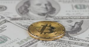 4k resolution of a cryptocurrency gold Bitcoin coin on a hundred usd dollars bills. Close-up, macro shot - slider