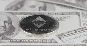 4k resolution of a cryptocurrency silver Ethereum coin on a hundred usd dollars bills. Close-up, macro shot - slider