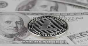 4k resolution of a cryptocurrency silver Litecoin coin on a hundred usd dollars bills. Close-up, macro shot - slider