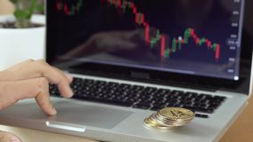 4k resolution of a man checking cryptocurrency chart and bitcoin coins next to him