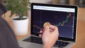 4k resolution of a man`s hand holding bitcoin coin and checking cryptocurrency chart