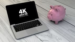 4k resolution screen and piggybank. Businnes concept: piggybank and 4k resolution screen laptop over wooden desk. All screen graphics are made up Royalty Free Stock Images