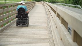 4k resolution video of a man on electrical wheelchair driving on wooden bridge. A man on electrical wheelchair driving on wooden bridge stock video footage