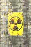 K?rnkraftsanl?ggning tecken som h?nger p? en tegelstenv?gg Indikering av n?rvaron av ett radioaktivt omr?de royaltyfri illustrationer