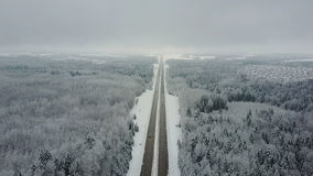 4K. Road in the frozen winter forest with driving cars. Aerial panoramic view. Vanishing point perspective stock footage