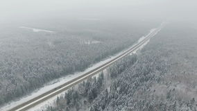 4K. Road in the winter forest with driving cars. Aerial view. Vanishing point perspective. stock video