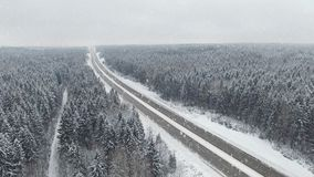 4K. Road in the winter forest with driving cars at snowfall. Aerial panoramic view. Vanishing perspective