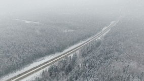 4K. Road in the winter forest with driving cars at snowfall. Aerial panoramic view. Vanishing point perspective stock video footage