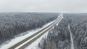 4K. Road in the winter forest with driving cars at snowfall. Aerial panoramic view. Vanishing point perspective stock video