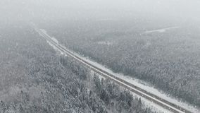 4K. Road in the winter forest with driving cars at snowfall. Aerial panoramic view. Vanishing perspective stock footage