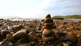 4K Rock stack balance and harmony on sea beach with evening ambient light and sound.  stock footage