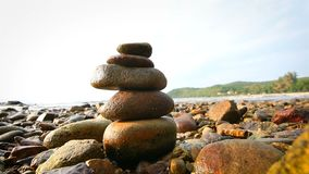 4K Rock stack balance and harmony on sea beach with evening ambient light and sound.  stock video