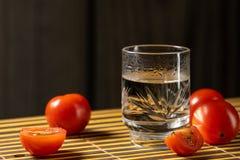 K?rsb?rsr?da tomater och vodka p? den matta hem- stilen arkivbilder