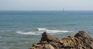 4k sailboat που πλέει στον ευρύ ωκεανό, την επιφάνεια κυμάτων θαλάσσιου νερού & τον παράκτιο βράχο απόθεμα βίντεο